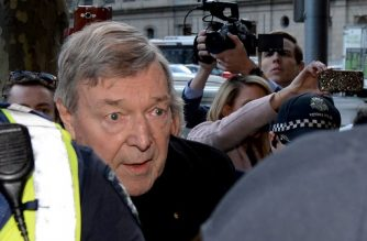 (FILES) This file photo taken on July 26, 2017 shows Cardinal George Pell arriving under heavy police protection for a filing hearing at the Melbourne Magistrates Court after being charged with sexual assault offences in Melbourne. Prosecutors on March 2, 2018 withdrew one of multiple historical sexual offence charges against Vatican finance chief Cardinal George Pell ahead of his committal hearing next week. / AFP PHOTO / MAL FAIRCLOUGH