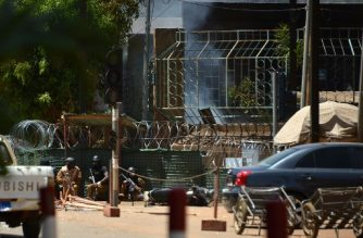 Security personnel take cover as smoke billows from The Institute Francais in Ouagadougou on March 2, 2018, as the capital of Burkina Faso came under multiple attacks targeting the French embassy, the French cultural centre and the country's military headquarters. Witnesses said five armed men got out of a car and opened fire on passersby before heading towards the embassy, in the centre of the city. Other witnesses said there was an explosion near the headquarters of the Burkinabe armed forces and the French cultural centre, which are located about a kilometre (half a mile) from the site of the first attack.  / AFP PHOTO / Ahmed OUOBA