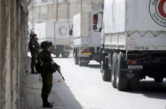 Russian soldiers stand guard as Syrian Arab Reb Crescent trucks carrying aid drive at the al-Wafideen checkpoint on the outskirts of Damascus neighbouring the rebel-held Eastern Ghouta region as they head towards the rebel-held enclave on March 5, 2018.   The convoy -- a joint operation between the ICRC, the Syrian Red Crescent and the United Nations -- consisted of 46 trucks, the ICRC communications chief in Syria, Pawel Krzysiek, said in a tweet   / AFP PHOTO / LOUAI BESHARA