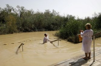 A picture taken on March 5, 2018 shows a Christian pilgrim taking pictures of another rising from the waters of the the Jordan river, at the baptismal site of Qasr al-Yahud near the border with Jordan in the occupied West Bank. The site receives thousands of Christian pilgrims who believe according to tradition that Jesus Christ was baptized by John the Baptist at the religious site, where a dozen abandoned monasteries lie surrounded by landmines left over from the 1967 Six-Day War. / AFP PHOTO / MENAHEM KAHANA