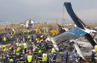"""Nepali rescue workers gather around the debris of an airplane that crashed near the international airport in Kathmandu on March 12, 2018. At least 40 people were killed and 23 injured when a Bangladeshi passenger plane crashed near Kathmandu airport March 12, an official said. """"Thirty-one people died at the spot and nine died at two hospitals in Kathmandu,"""" police spokesman Manoj Neupane told AFP, adding another 23 were injured. There were 67 passengers and four crew on board the US-Bangla Airlines plane from Dhaka.   / AFP PHOTO / Prakash MATHEMA"""
