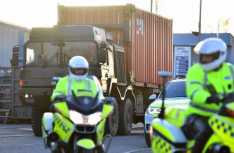Police motorcycle out-riders escort a British army truck, carrying a freight container laden with the car of Sergei Skripal, as it is driven from the Churchfields industrial estate in Salisbury, southern England, on March 16, 2018, as part of investigations and operations in connection with the major incident after an apparent nerve agent attack in Salisbury on March 4. NATO Secretary General Jens Stoltenberg said March 16, the alliance did not want a return to Cold War hostilities with Russia while expressing support for Britain's strong stance on the nerve agent attack. / AFP PHOTO / Ben STANSALL