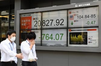 Pedestrians walk past an electronics stock indicator showing share prices on the Tokyo Stock Exchange (L) and the foreign exchange rate between the US dollar and Japanese yen (R), in Tokyo on March 23, 2018. Tokyo stocks plunged early on March 23, with the benchmark Nikkei 225 index falling three percent on revived trade war fears as US President Donald Trump unveiled tariffs on Chinese imports. / AFP PHOTO / Kazuhiro NOGI