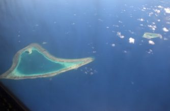 This picture taken on April 21, 2017 shows an aerial view of reefs in the disputed Spratly islands. Philippine Defence Secretary Delfin Lorenzana flew to a disputed South China Sea island on April 21, brushing off a challenge by the Chinese military while asserting Manila's territorial claim to the strategic region. / AFP PHOTO / Ted ALJIBE
