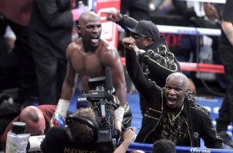 Boxer Floyd Mayweather Jr. and his father Floyd Mayweather Sr. celebrate his 10th round TKO victory over mixed martial arts star Conor McGregor at the T-Mobile Arena in Las Vegas, Nevada.  Undefeated welterweight boxing world champion Mayweather overcame a spirited start from a brave but outclassed McGregor, dominating from the fourth round onwards. The end came with a tired McGregor doubled over on the ropes as Mayweather landed two hard left hooks.  / AFP PHOTO / John Gurzinski