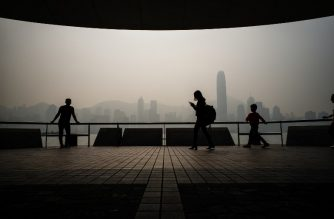 FILE PHOTO: Tourists visit a Kowloon promenade as smog engulfs Hong Kong's famous skyline (back) on January 22, 2018. Hong Kong's famous skyline was engulfed in smog on January 22, with residents urged to stay indoors. / AFP PHOTO / Anthony WALLACE