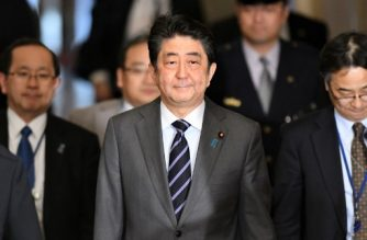 Japan's Prime Minister Shinzo Abe (C) walks to a session of the House of Representatives Budget Committee at parliament in Tokyo on February 5, 2018. Japan on February 5 welcomed a victory by the ruling bloc-backed candidate in a mayoral election in southern Okinawa, seen as a key to pushing forward a decades-old plan to relocate a US military base. / AFP PHOTO / Kazuhiro NOGI