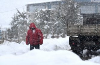 A man walks under heavy snow in Pogradec, southeastern Albania, on February 27, 2018. A blast of Siberian weather sent temperatures plunging across much of Europe on February 27, carpeting palm-lined beaches in snow and prompting warnings for the homeless and elderly people. / AFP PHOTO / Gent SHKULLAKU