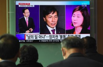 People watch a television news report showing a picture of Kim Ji-eun (R on television), a secretary of Ahn Hee-jung, at a railway station in Seoul on March 6, 2018. Ahn, the former South Korean presidential contender of the ruling Democratic Party stepped down as a provincial governor on March 6 and announced his retirement from politics after a secretary accused him of multiple rapes. / AFP PHOTO