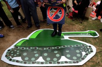 A Thai anti-junta activist holds a banner saying stop prolonging power, stop delaying elections while stepping on a cartoon of a military tank during a pro-democracy rally at a university field in Bangkok on March 10, 2018. /AFP PHOTO / Pattarachai Preechapanich