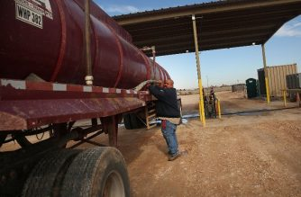 An oilfield worker fills his truck with water at a filling station before heading to a drilling site in the Permian Basin oil field on January 20, 2016 in the oil town of Andrews, Texas.    Spencer Platt/Getty Images/AFP