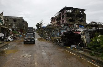 A military vehicle passes bombed-out buildings inside the battle area of Bangolo district in Marawi on October 17, 2017.  / AFP photo / Ted Aljibe