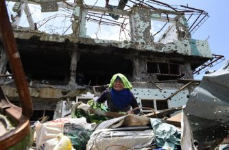 A resident tries to collect salvageable belongings from her destroyed house during a visit to the main battle area in Marawi City, in southern island of Mindanao on April 1, 2018. After fleeing for their lives nearly a year ago, residents of the battle-scarred Philippine city of Marawi made their first visit back on April 1 to dig through the rubble that was once their homes. / AFP PHOTO / TED ALJIBE