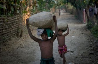 This photograph taken on March 10, 2018, Rohingya children carry sacks at Shan Taung village in the outskirt of Mrauk U township located in Rakhine State close to Bangladesh border.   The villagers are among some 500,000 Rohingya who remain in Myanmar, spared by wealth, commercial ties with their Rakhine neighbours, luck or just living isolated from the recent violence. / AFP PHOTO / Phyo Hein KYAW