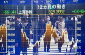Pedestrians are reflected on a stock indicator showing share prices of the Shanghai B-share stock price in Tokyo on April 5, 2018. Tokyo stocks closed higher on April 5 as fears of a US-China trade war eased and the yen weakened against the dollar. / AFP PHOTO / Behrouz MEHRI