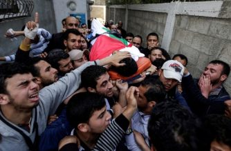 Mourners and journalists carry the body of Palestinian journalist Yasser Murtaja, during his funeral in Gaza City on April 7, 2018. Among those killed at Friday's protest was Yasser Murtaja, a photographer with the Gaza-based Ain Media agency, who died from his wounds after being shot, the local health ministry said.   Murtaja's company confirmed his death, with witnesses saying he was close to the front of the protests in Southern Gaza when he was hit. / AFP PHOTO / MAHMUD HAMS