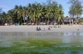 Tourists relax as algae turns the water green at Boracay beach, Malay town, in central Philippines on April 17, 2018, ahead of its closure.  The Philippines is set to deploy hundreds of riot police to top holiday island Boracay to keep travellers out and head off potential protests ahead of its six-month closure to tourists, the government said April 17. / AFP PHOTO / STR