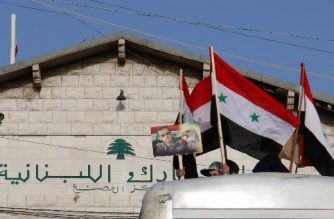 Men raise Syrian flags and a picture of Syrian President Bashar al-Assad dressed in a Field Marshal's camouflage uniform from the roof of a bus carrying Syrian refugees evacuated from the southern Lebanese village of Shebaa, as it passes through the Masnaa crossing on the Lebanon-Syria border leading to Damascus on April 18, 2018, returning them home to their village of Beit Jinn in the southwestern Damascus countryside. / AFP PHOTO / HASSAN JARRAH