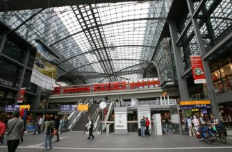 (FILES) In this file photo taken on August 2, 2007, passengers walk through Berlin's Hauptbahnhof main railway station as a train stands on an upper platform. The discovery of an unexploded World War II bomb will force a mass evacuation around Berlin's central railway station on April 20, 2018, covering several government ministries and a hospital, police said. / AFP PHOTO / Barbara SAX
