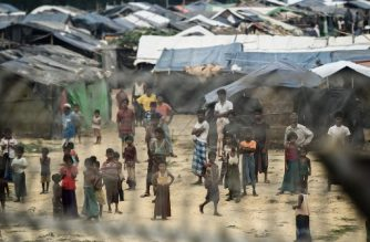 """Rohingya refugees gather near their shelters in the """"no man's land"""" behind Myanmar's boder lined with barb wire fences in Maungdaw district, Rakhine state bounded by Bangladesh on April 25, 2018. Myanmar government said on April 15, it repatriated on April 14 the first family of Rohingya out of some 700,000 refugees who have fled a brutal military campaign, a move slammed by a rights group as a PR stunt ignoring UN warnings that a safe return is not yet possible. / AFP PHOTO / Ye Aung THU"""