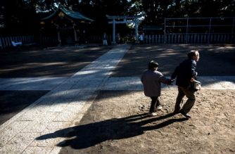 In this picture taken on January 10, 2017, Kanemasa Ito (R) and his dementia-stricken wife Kimiko walk in the courtyard of Takaishi shrine in Kawasaki. One of the world's most rapidly aging and long-lived societies, Japan is at the forefront of an impending global healthcare crisis. Authorities are bracing for a dementia timebomb and their approach could shape policies well beyond its borders. / AFP PHOTO / BEHROUZ MEHRI / TO GO WITH Japan-society-ageing-dementia,FEATURE by Natsuko FUKUE