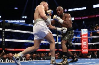 LAS VEGAS, NV - AUGUST 26: (R-L) Floyd Mayweather Jr. throws a punch at Conor McGregor during their super welterweight boxing match on August 26, 2017 at T-Mobile Arena in Las Vegas, Nevada.   Christian Petersen/Getty Images/AFP