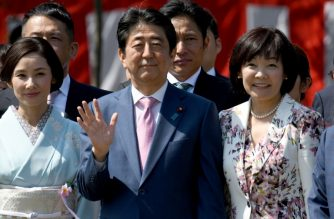 Japanese Prime Minister Shinzo Abe (C) and his wife Akie (R) pose with actress Yo Yoshida (L) and other entertainers during his garden party in Tokyo on April 21, 2018. / AFP Photo / Toshifumi Kitamura