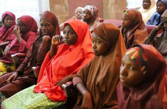 Released Nigerian school girls who were kidnapped by Boko Haram from their school in Dapchi, in the northeastern state of Yobe, sit at the Presidential Villa in Abuja before meeting with the president on March 23, 2018. / AFP Photo / Philip Ojisua