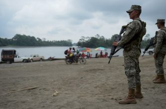Colombian marines stand guard along the Mira river in Imbili, Tumaco Municipality, in the Colombian department of Narino near the border with Ecuador, on April 15, 2018. / AFP Photo / Raul Arboleda