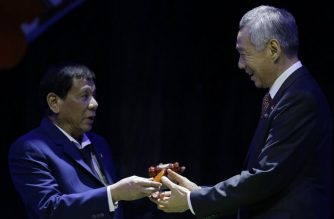 President Rodrigo Duterte (L) hands over the gavel to Singapore Prime Minister Lee Hsien Loong during a transfer of ASEAN Chairmanship at the closing ceremonies of the 31st Association of Southeast Asian Nations (ASEAN) Summit in Manila on November 14, 2017. / AFP Photo / Pool / Aaron Favila
