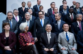 International Monetary Fund Managing Director Christine Lagarde looks to US Secretary of the Treasury Steven Mnuchin  during a group photo of G-20 Finance Ministers and Central Bank Governors at the 2018 IMF/World Bank spring meetings April 20, 2018 in Washington, DC. / AFP Photo / Brendan Smialowski