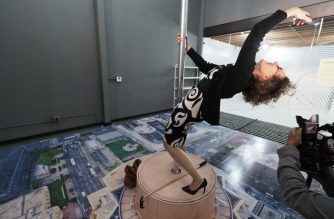 "Visitor Nina Crowe takes a ""rooftop"" selfie - simulating the perspective of being on top of the tallest building in Los Angeles - at the Museum of Selfies, in Glendale, California, March 29, 2018. / AFP photo / Robyn Beck"