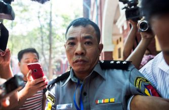 Myanmar deputy police major Moe Yan Naing (C) leaves the court following the ongoing trial of two detained journalists in Yangon on April 20, 2018. / AFP Photo/ Sai Aung Main