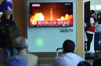 People watch a television news showing a file footage of North Korean missile launch, at a railway station in Seoul on April 21, 2018.  / AFP Photo/ Jung Yeon-je