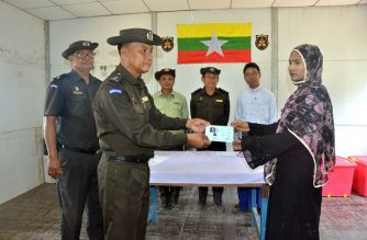 This handout photo released by the Myanmar News Agency on April 15, 2018 and taken April 14 shows a Myanmar immigration official (2nd L) handing over identification documents to an unidentified Rohingya woman (R) belonging to a five-member Rohingya family at the Taungpyoletwei town repatriation camp in Maungdaw near the Bangladesh border. / AFP Photo /Myanmar News Agency
