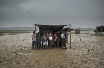 (FILES) In this file photo taken on October 6, 2017 Rohingya refugees take shelter from the rain at Nayapara refugee camp in Bangladesh's Ukhia district. Humanitarian agencies have been warning for months about the danger posed by the impending 2018 monsoon, due to start in June, to the welfare of refugees who live cheek by jowl in cramped tents on hillsides, following a mass exodus from Myanmar in 2017.  / AFP PHOTO / FRED DUFOUR