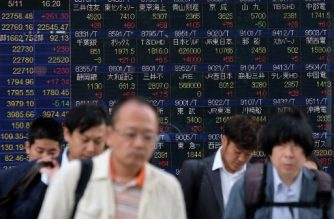 Pedestrians walk past a stock indicator showing stock prices of Japanese companies listed on the Tokyo Stock Exchange in Tokyo on May 11, 2018. Tokyo stocks leapt on May 11, led by rallies in high-tech shares, after Wall Street gains outweighed concern about geopolitical risk over US plans to open an embassy in Jerusalem next week. / AFP PHOTO / Kazuhiro NOGI