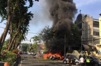 """This handout photo from the Surabaya local government (Pemerintah Kota Surabaya) taken on May 13, 2018 and received by AFP on May 14, 2018 shows police at the site of a blast outside the Gereja Pantekosta Pusat Surabaya (Surabaya Centre Pentecostal Church) in Surabaya.   A series of blasts, including at least one suicide bombing, struck churches in Indonesia on May 13, killing at least 11 people and wounding dozens in the deadliest attack for years in the world's biggest Muslim-majority country. / AFP PHOTO / PEMERINTAH KOTA SURABAYA / Andy PINARIA / RESTRICTED TO EDITORIAL USE - MANDATORY CREDIT """"AFP PHOTO / PEMERINTAH KOTA SURABAYA / ANDY PINARIA"""" - NO MARKETING - NO ADVERTISING CAMPAIGNS - DISTRIBUTED AS A SERVICE TO CLIENTS"""