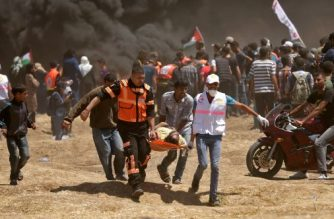Palestinians carry a demonstrator injured during clashes with Israeli forces near the border between the Gaza strip and Israel east of Gaza City on May 14, 2018, as Palestinians readied for protests over the inauguration of the US embassy following its controversial move to Jerusalem. The US moves its embassy in Israel to Jerusalem later Monday after months of global outcry, Palestinian anger and exuberant praise from Israelis over President Donald Trump's decision tossing aside decades of precedent. There are concerns that the Gaza protests less than 100 kilometres (60 miles) away will turn deadly if Palestinians attempt to damage or cross the fence with Israeli snipers positioned on the other side. / AFP PHOTO / MAHMUD HAMS