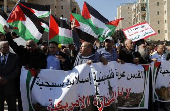 """Arab demonstrators protest in front the new United States embassy in Jerusalem on May 14, 2018. The banner reads in Arabic """" Jerusalem is Arab, Palestinian, Moslem, Christian"""".  The United States moved its embassy in Israel to Jerusalem after months of global outcry, Palestinian anger and exuberant praise from Israelis over President Donald Trump's decision tossing aside decades of precedent. / AFP PHOTO / AHMAD GHARABLI"""