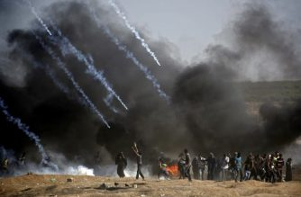 Tear gas is fired at protestors during clashes with Israeli forces near the border between the Gaza strip and Israel, east of Gaza City on May 14, 2018, following the the controversial move to Jerusalem of the United States embassy.  Fifty-two Palestinians were killed by Israeli fire during violent clashes on the Gaza-Israel border coinciding with the opening of the US embassy in Jerusalem, the health ministry in the strip announced.  / AFP PHOTO / THOMAS COEX