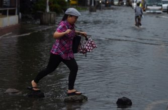 A pedestrian steps on stones to cross a flooded street in Manila on August 13, 2016, after heavy downpours overnight. Floods inundated major thoroughfares in the capital late on August 12, after heavy rains brought about by southwest moonson, authorities said on August 13. / AFP PHOTO / TED ALJIBE