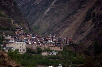 This picture taken on April 20, 2018 shows Chinese flags flying above Qiang minority homes in the village of Kuopo in Longxi township in Sichuan province. The May 12, 2008, earthquake left 87,000 people dead or missing across Sichuan, with over 30,000 of them Qiang -- 10 percent of the group's population. China on May 12, 2018  marks the 10-year anniversary of the quake. / AFP Photo/ Johannes Eisele