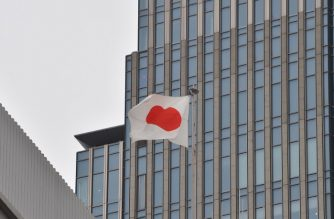 (FILE) Japanese national flag flies on the roof of a building in Tokyo on November 14, 2016. / AFP Photo / Kazuhiro Nogi
