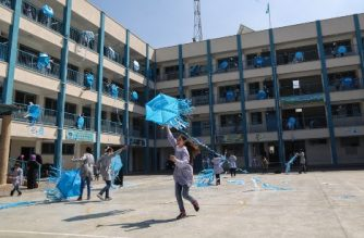 "Palestinian schoolgirls fly kites outside their classrooms at a school belonging to the United Nations Relief and Works Agency for Palestinian Refugees (UNRWA) in Gaza City on March 12, 2018 as a protest against US aid cuts. On January 16, Washington held back $65 million that had been earmarked for the UN Relief and Works Agency for Palestinian refugees (UNRWA), but the State Department denied the freeze was to punish the Palestinian leadership, which has cut ties with President Donald Trump's administration following his recognition of Jerusalem as Israel's capital last year, with a spokeswoman saying it was linked to necessary ""reform"" of UNRWA. / AFP PHOTO / MAHMUD HAMS"