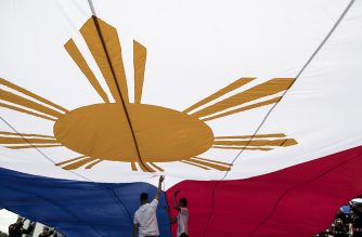 Workers of the National Historical Commission of the Philippines (NHCP) assist in fixing the national flag during the 120th Independence Day celebration at Rizal Park in Manila on June 12, 2018. / AFP PHOTO / NOEL CELIS