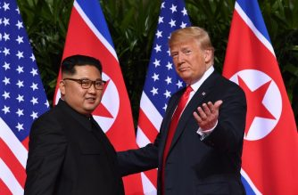 US President Donald Trump (R) gestures as he meets with North Korea's leader Kim Jong Un (L) at the start of their historic US-North Korea summit, at the Capella Hotel on Sentosa island in Singapore on June 12, 2018. Donald Trump and Kim Jong Un have become on June 12 the first sitting US and North Korean leaders to meet, shake hands and negotiate to end a decades-old nuclear stand-off. / AFP PHOTO / SAUL LOEB