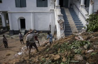Workers clear debris after a landslide damaged the hilltop Kyeik Than Lan? pagoda in Mawlamyine capital of Mon state on June 18, 2018 following heavy rains. Flooding in southern Myanmar caused a landslide at a famed pagoda, submerged homes and displaced residents, according to state media and AFP correspondents on the scene, as the monsoon season picks up strength. / AFP PHOTO / Ye Aung THU