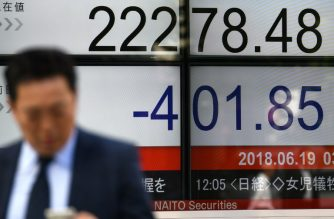 A pedestrian walks past a stock indicator displaying the closing rate of the Tokyo Stock Exchange in Tokyo on June 19, 2018. Tokyo's benchmark Nikkei index dropped more than 1.7 percent on June 19, with investors jittery over US-China trade tensions and a strong yen. / AFP PHOTO / Toshifumi KITAMURA