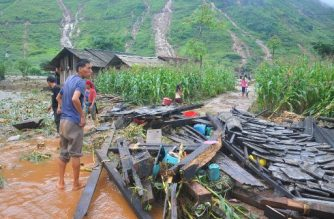In this picture taken on June 25, 2018 shows a Vietnamese man looking at the debris of his house destroyed by flash floods  in northern Ha Giang province. Flash floods and landslides killed 15 people in Vietnam's mountainous north, officials said on June 26, 2018, after storms ravaged homes and wiped out crops and infrastructure. / AFP PHOTO / Str